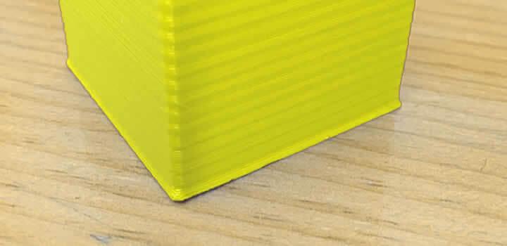 Bordas da impressão saindo da peça ou pata de elefante com filamento 3d pla amarelo impresso em cima de mesa de madeira