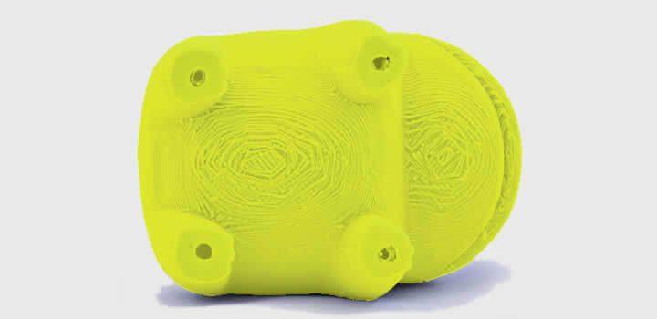 Foto de uma peça amarela impressa 3d com filamento 3d tirada da parte de baixo de uma peça que usou suporte demonstrando dificuldade com acabamento