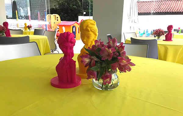 Foto de uma festa de criança focando uma mesa com toalha amarela e peças 3d impressas em filamento 3d amarelo e rosa dos personagens frozen
