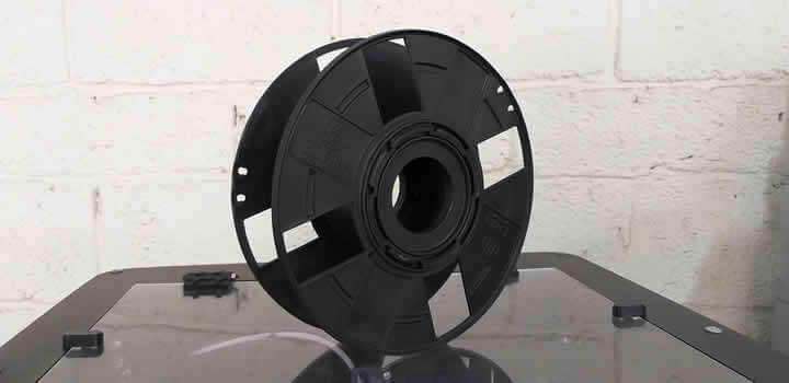 foto de carretel de filamento para impressora 3d vazio em cima de impressora 3d com fundo de parede em tijolos