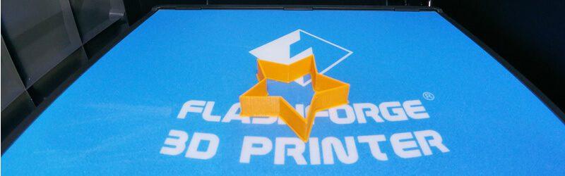 Foto de uma forminha laranja impressa com filamento PLA laranja basic da 3D Fila dentro da uma impressora FlashForge Guider IIS depois da modelagem 3d com o software tinkercad