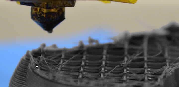 foto mostrando impressão 3d parada no meio com impressora 3d existe uma peça mal acabada mostrando o infill ou preenchimento