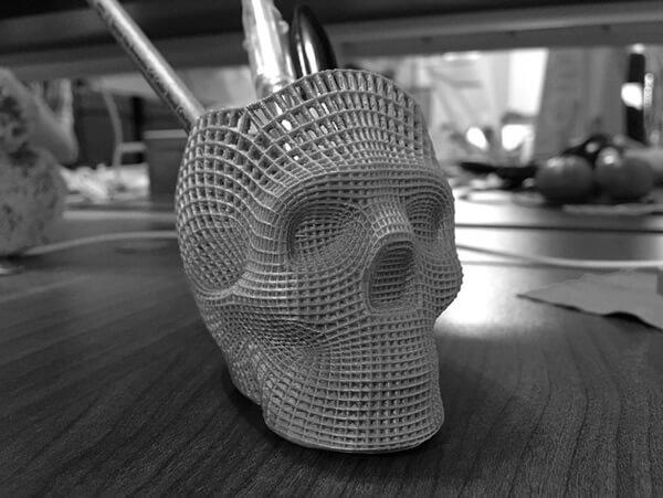foto em tons de cinza de um porta lápis de caveira impresso 3d com impressora 3d e algumas canetas, em cima de uma mesa