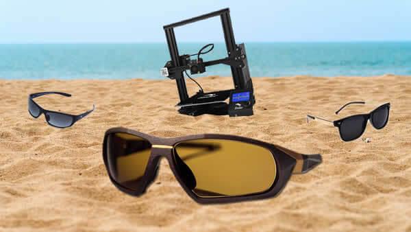imagem com 3 oculos de sol escuros e uma impressora na areia