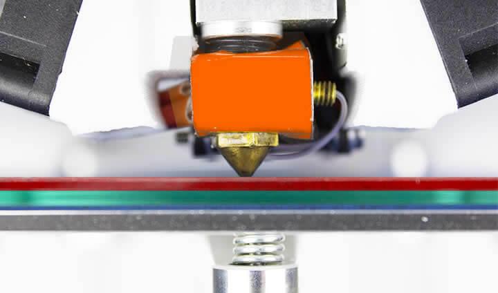 foto com zoom do bico de uma impressora 3d muito próximo da mesa , espremendo o filamento